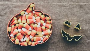 candy corn in pumpkin shaped dish on table
